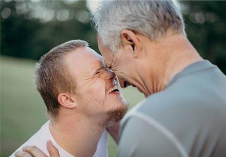 Kehitysvammainen poika ja vanhempi mies katsovat toisiaan silmiin ja nauravat. Heidän otsansa koskettavat toisiaan ja miehen kädet lepäävät kevyesti pojan olkapäillä.