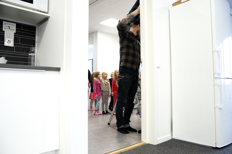 Kuvassa kiinnitetään esikouluaisten tekemään taideteosta Ahveniston sairaalan projektitoimiston seinälle