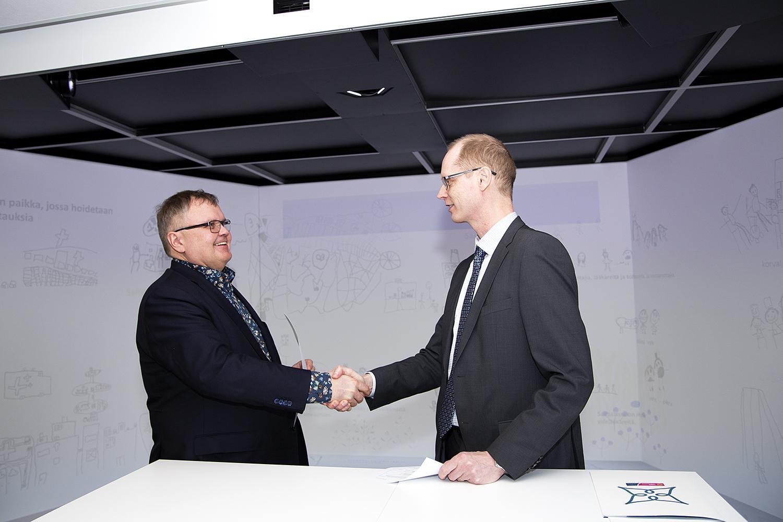 Sairaanhoitopiirin johtaja Seppo Ranta kättelee Elenia Lämpö Oy:n toimitusjohtaja Matti Tynjälän kanssa.